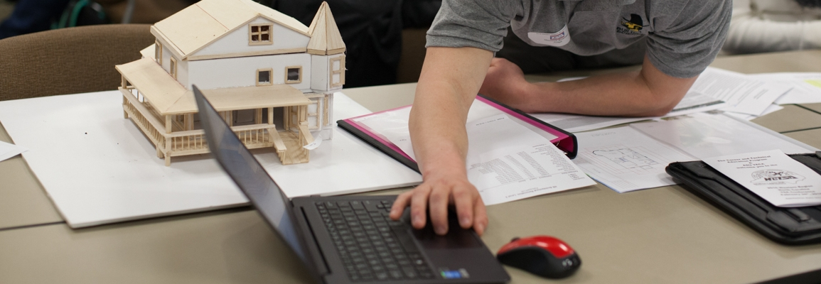 student working on laptop with architectural model on desk next to him